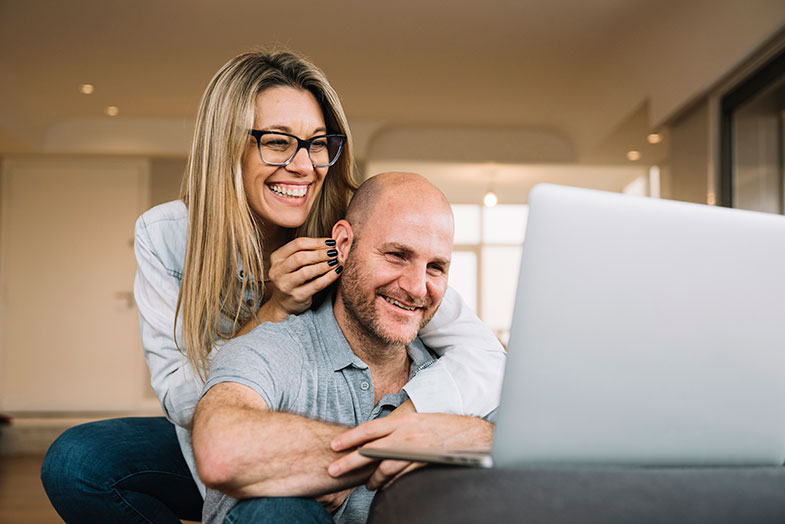 pareja abrazada mirando la computadora
